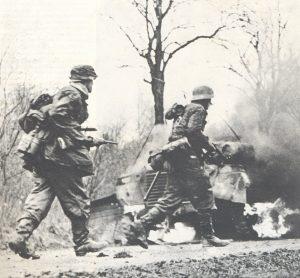 Njemački pješaci napreduju pored zapaljenog oklopnog automobila.