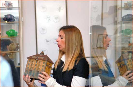 """Voditeljica Muzeja, Melita Jesih Matić s jednom od najzanimljivijih kasica, """"Dobrotvornom škrabicom"""" kulturnog društva Napredak, na kojoj se nalazi hrvatski grb koji započinje bijelim poljem."""